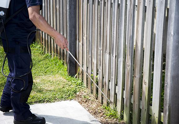 exterminator spraying fence